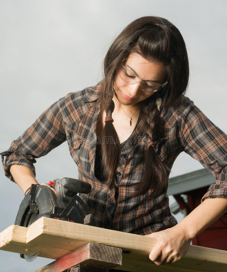 Den Craftsperson kvinnan använder bitande trä för cirkelsågen fotografering för bildbyråer