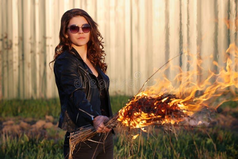Den dåliga kvinnan i solglasögon och ett svart omslag som utomhus rymmer en fackla royaltyfri foto