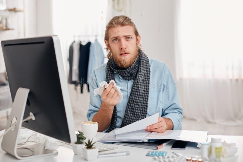 Den dåligt skäggiga mannen nyser, använder näsduken, känner sig opasslig, har influensa Sjuka manliga den tröttade kontorsarbetar fotografering för bildbyråer