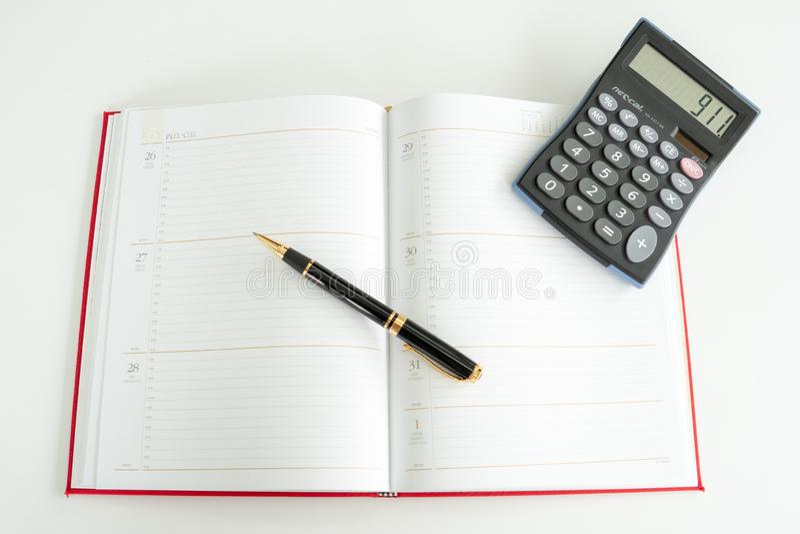 Den dagliga planboken fördelade ut med en reservoarpenna och en räknemaskin på den arkivbild