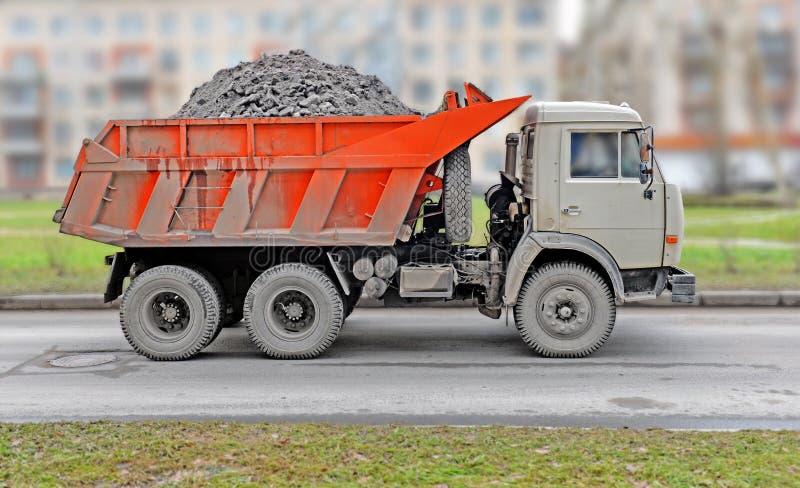 Den dammiga lastbilen med en röd kropp royaltyfria foton