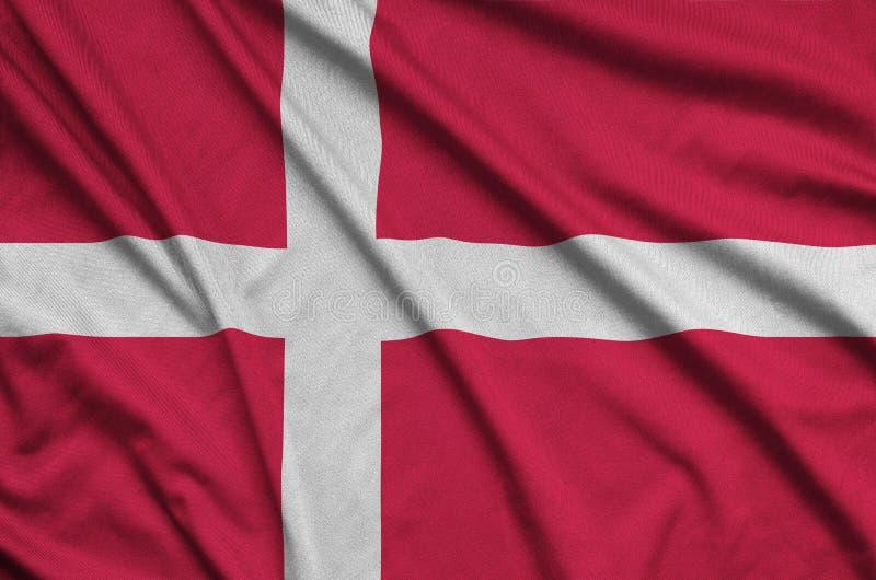 Den Danmark flaggan visas på ett sporttorkduketyg med många veck Baner för sportlag arkivfoto