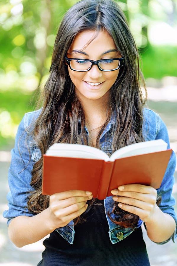 Den Dark-haired unga kvinnan läser red arkivfoto