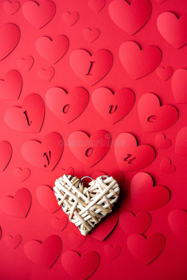 Den dekorativa beståndsdelen i form av en hjärta ligger på bakgrunden av rött papper med sned hjärtor fotografering för bildbyråer