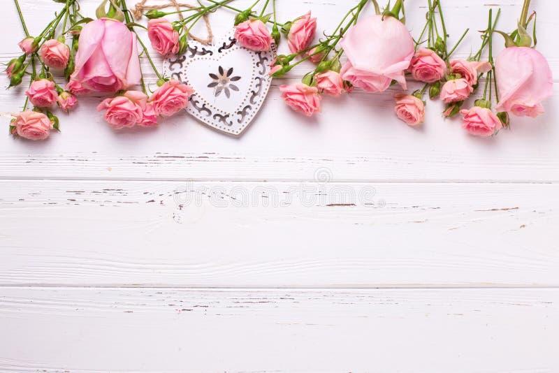 Den dekorativa hjärta och gränsen från rosa rosor blommar på vit uppvaktar fotografering för bildbyråer