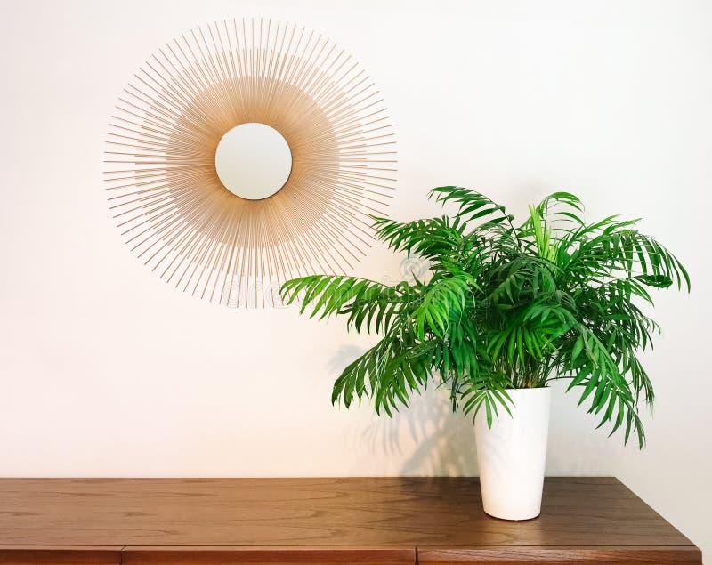 Den dekorativa runda spegeln och mottagningsrummet gömma i handflatan växten på en skänk arkivfoton