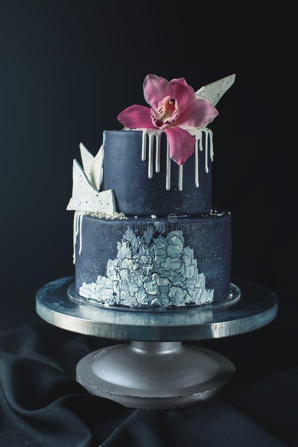 Den dekorerade svarta bröllopstårtan med vit choklad och orkidén blommar fotografering för bildbyråer