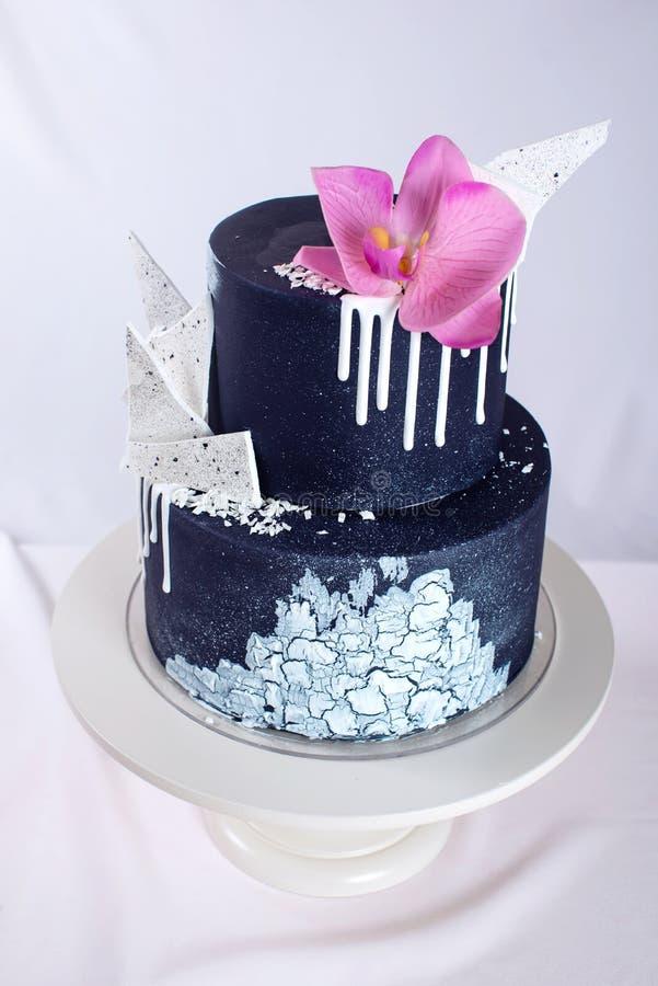 Den dekorerade svarta bröllopstårtan med vit choklad och orkidén blommar royaltyfri bild