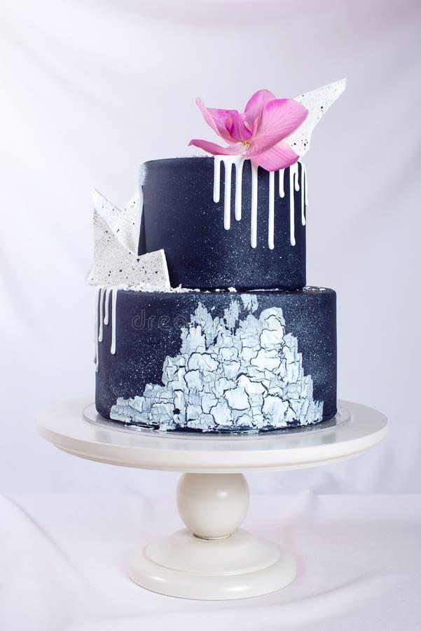 Den dekorerade svarta bröllopstårtan med vit choklad och orkidén blommar royaltyfri fotografi