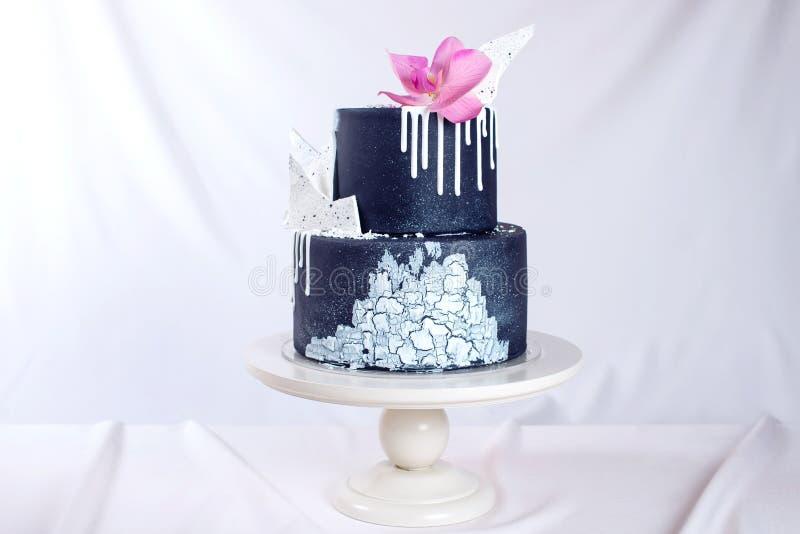 Den dekorerade svarta bröllopstårtan med vit choklad och orkidén blommar royaltyfria foton