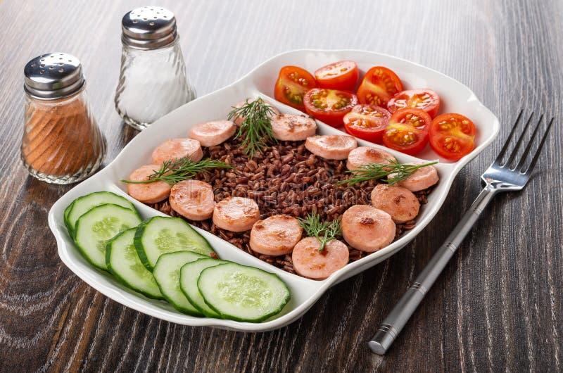 Den delade maträtten med stekte korvar, röda ris, gurkor, tomaten, gaffel, saltar och pepprar på trätabellen arkivbilder