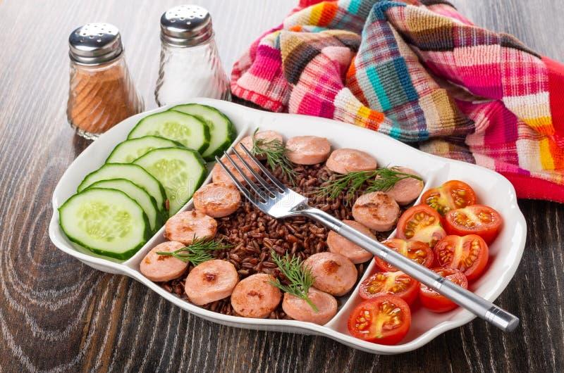 Den delade maträtten med stekte korvar, röda ris, gurkor, tomaten, gaffel, saltar och pepprar, servetten på tabellen royaltyfri fotografi