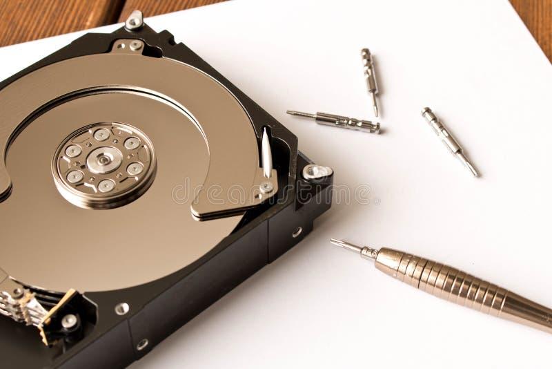 Den demonteraa hårddisken med en variation av skruvmejslar close upp arkivbild