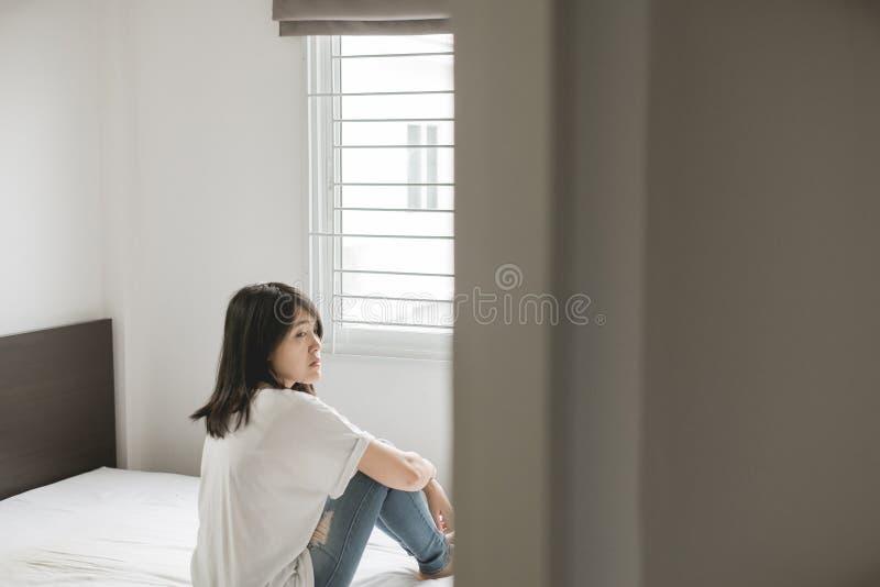 Den deprimerade asiatiska kvinnan har en huvudvärk- och känslasorg i sovrum royaltyfri foto