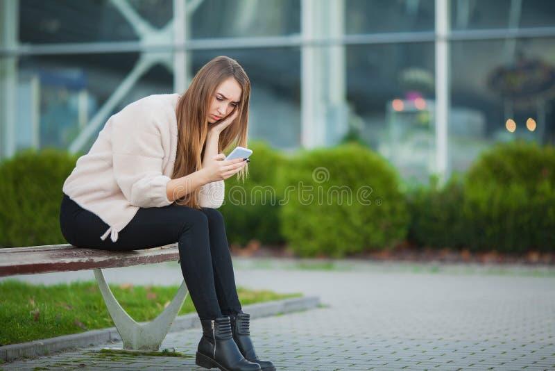 Den deprimerade kvinnan som sitter i en stad, parkerar på en bänk royaltyfri foto