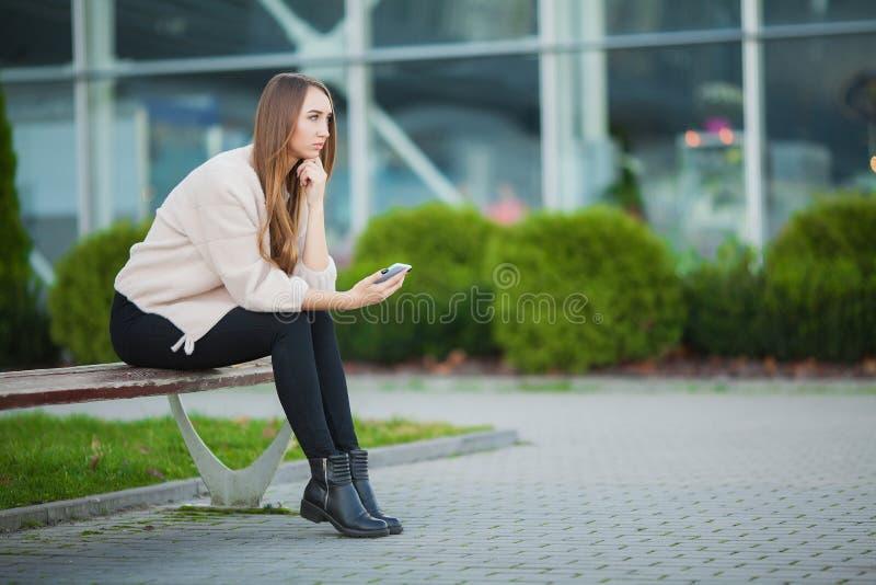 Den deprimerade kvinnan som sitter i en stad, parkerar på en bänk arkivbilder