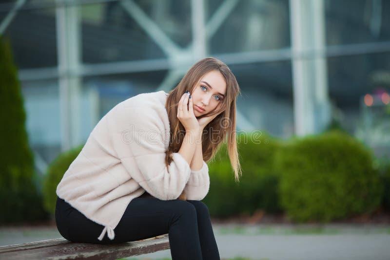 Den deprimerade kvinnan som sitter i en stad, parkerar på en bänk royaltyfria foton