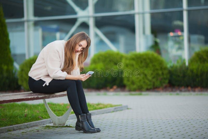 Den deprimerade kvinnan som sitter i en stad, parkerar på en bänk royaltyfri bild