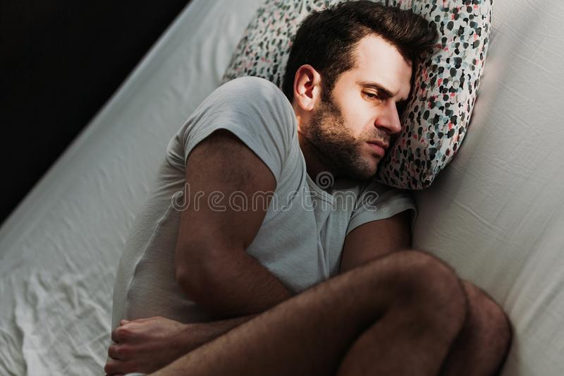 Den deprimerade mannen smärtar in på sängen royaltyfri foto