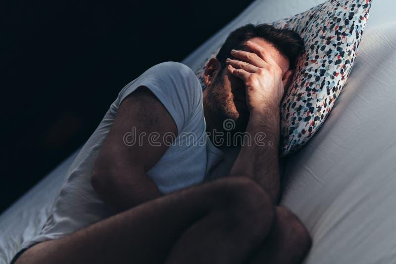 Den deprimerade mannen smärtar in på sängen royaltyfria foton