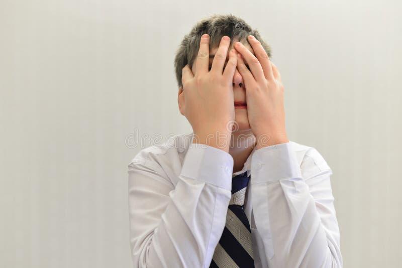 den deprimerade tonåringpojken täckte hans framsida med hans händer arkivbilder