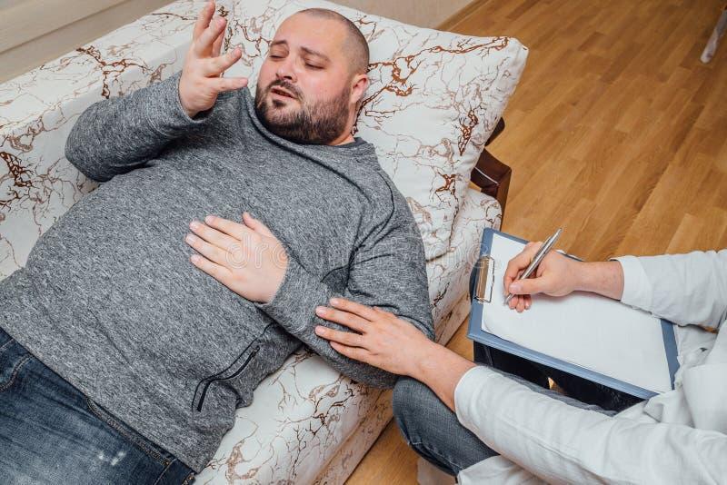 Den deprimerande mannen besöker en psykolog Psychologist som skriver anmärkningar och, uppmuntrar hans patient fotografering för bildbyråer