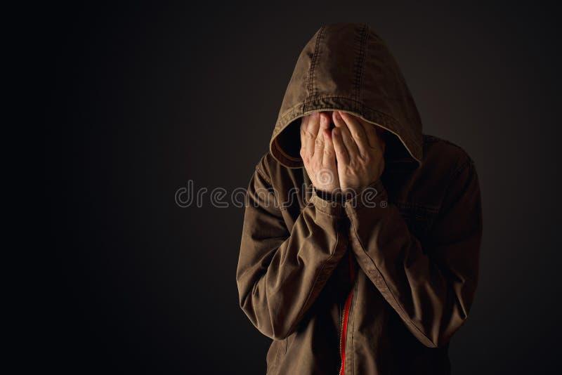 Den deprimerande mannen i med huva omslag gråter royaltyfri bild