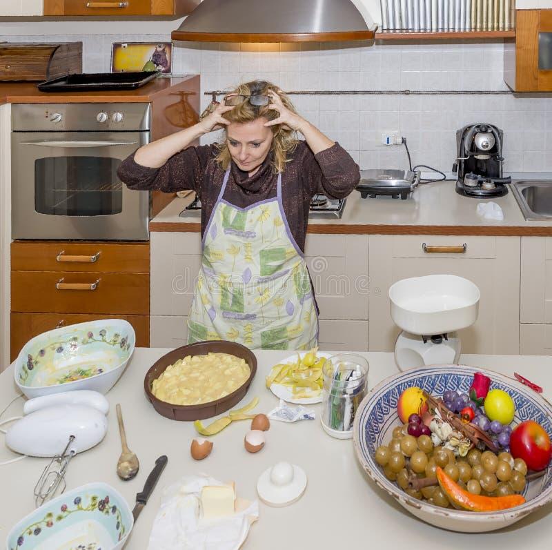 Den desperata hemmafrun med händer i håret för röra i kök ska hon måste fixa royaltyfri foto