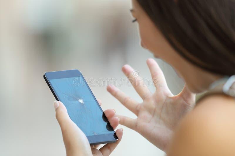 Den desperata kvinnan som ser hennes telefon, kraschade skärmen royaltyfri bild