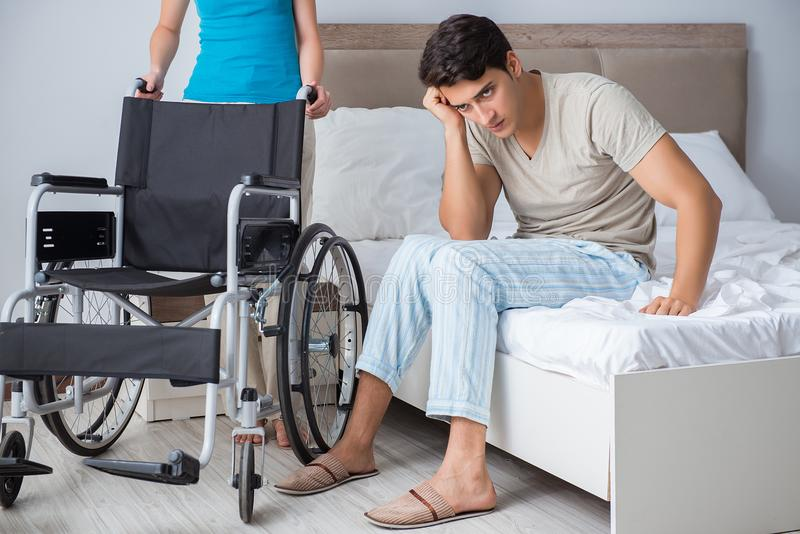 Den desperata mannen på rullstolen med hans ledsna fru royaltyfria bilder