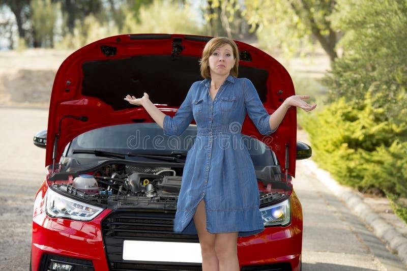Den desperata och förvirrade kvinnan strandade på vägrenen med brutet bilmotorfel eller krascholycka royaltyfri foto