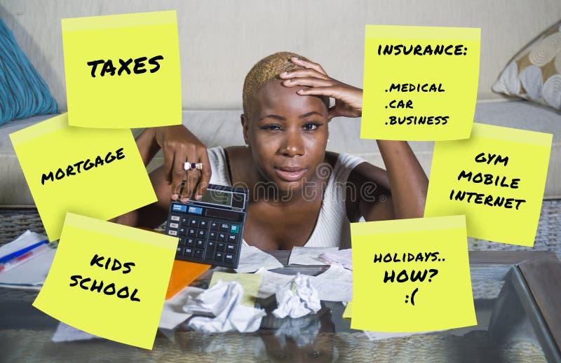 Den desperata och frustrerade svarta afro amerikanska redovisningen för kvinnahemhjälp oroade om pengar som betalar skatter som b royaltyfri bild