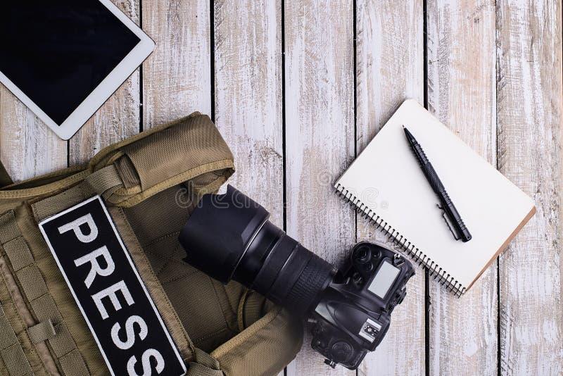Den Digitala kameran, anteckningsboken med pennan, kroppharnesken och minnestavlan trycker på com royaltyfri bild