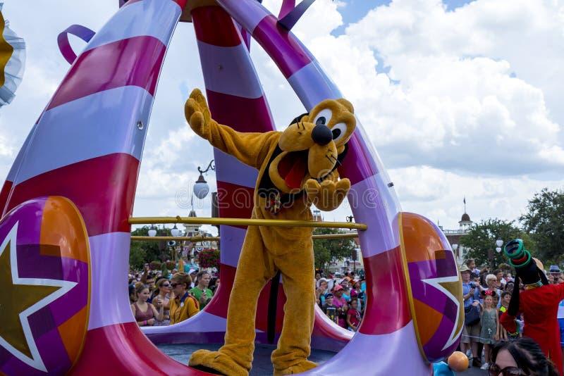 Den Disney världen Orlando Florida Magic Kingdom ståtar pluto arkivfoto