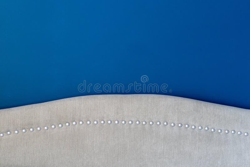 Den djupa kungliga blåa målade väggen med ett stoppat huvudgavelslut upp, uppvisning försilvrar spikar huvud och den beigea tygde royaltyfria bilder