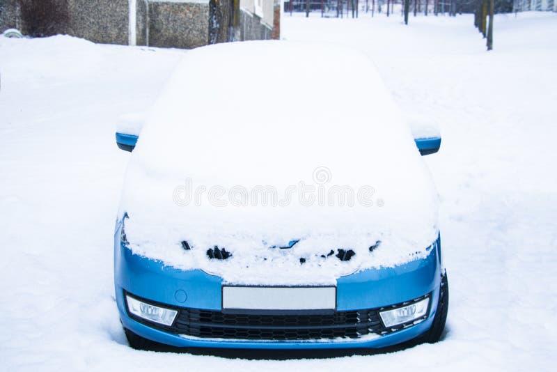 Den djupfrysta bilen täckte snö på vinterdagen, vindrutan för främre fönster för sikt och huven på snöig bakgrund arkivfoto