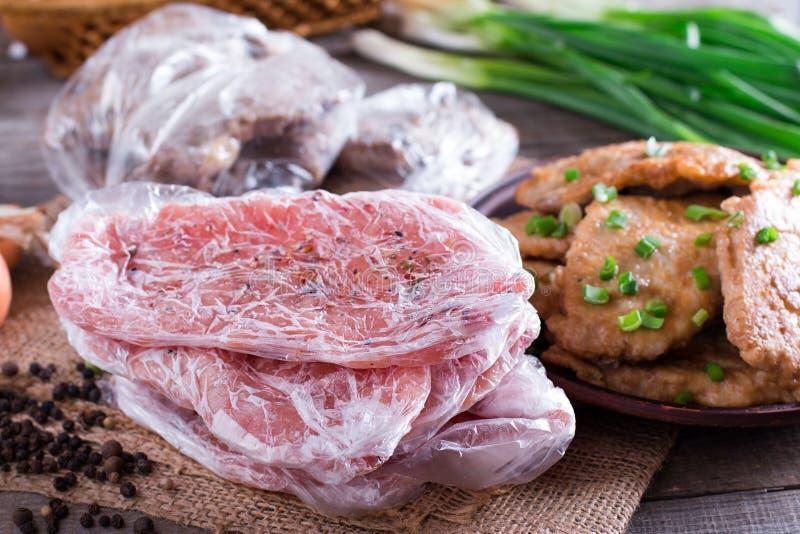 Den djupfrysta griskötthalsen hugger av kött- och grisköttschnitzeln i en platta royaltyfri foto