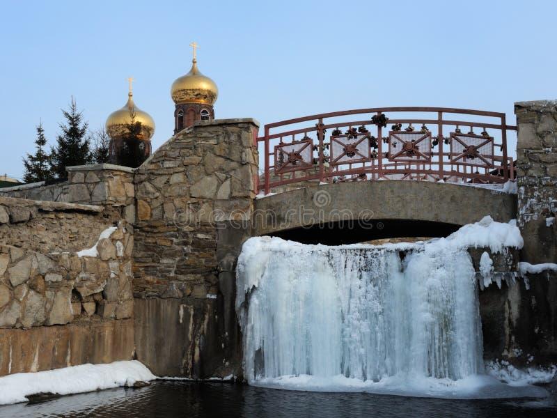 Den djupfrysta vattenfallet av det heliga vattnet under spången royaltyfri bild