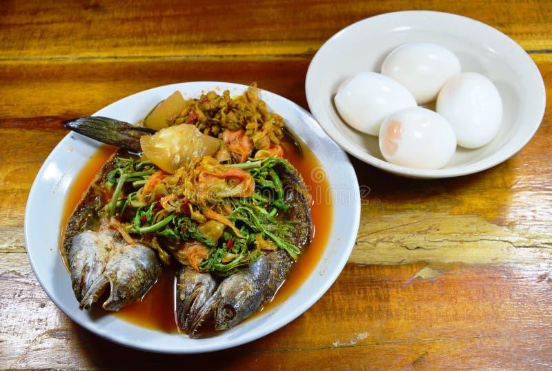 Den djupt stekte randiga ormhuvudfisken i blandad varm och sur soppa äter med det kokta ägget royaltyfri foto