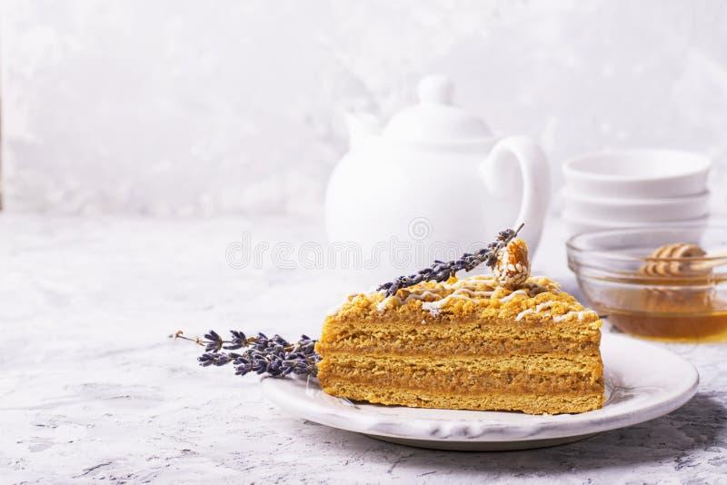 Den doftande hemlagade honungkakan med muttrar och lavendel på grå färger hårdnar bakgrund som är ny i horisontalversionen royaltyfri foto
