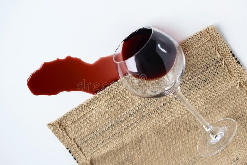 Den dråsade glass bägaren på tabellen från den häller ut rött vin, begreppet fotografering för bildbyråer