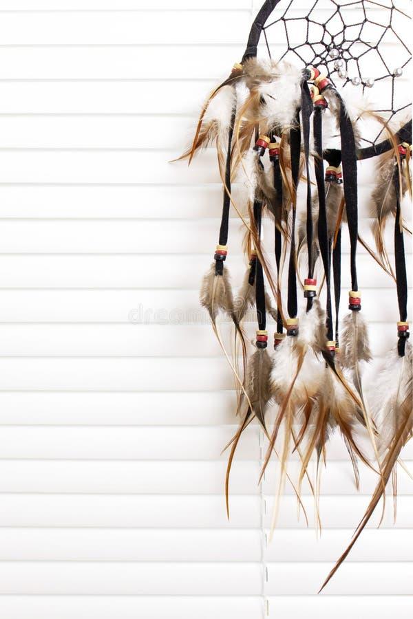 Den dröm- stopparen med fjädrar dragar och pryder med pärlor repet som hänger, vita fönsterrullgardiner på bakgrund Handgjorda Dr royaltyfri foto