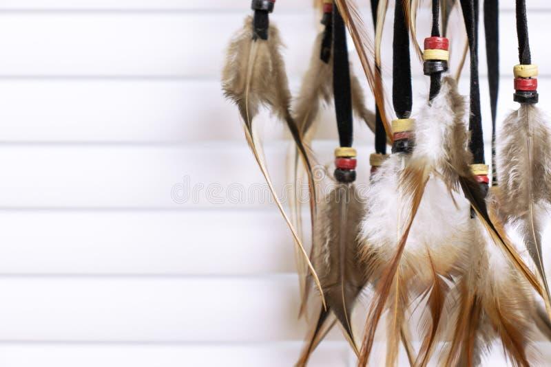 Den dröm- stopparen med fjädrar dragar och pryder med pärlor repet som hänger, vita fönsterrullgardiner på bakgrund Handgjorda Dr royaltyfria foton