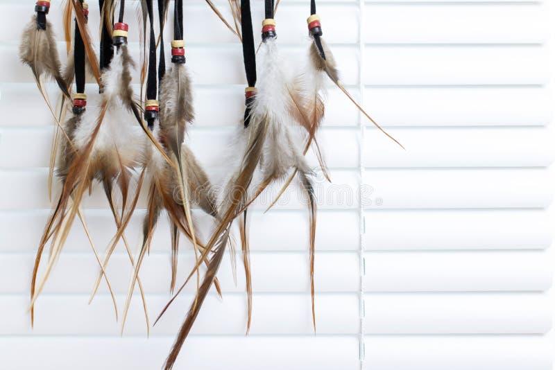 Den dröm- stopparen med fjädrar dragar och pryder med pärlor repet som hänger, vita fönsterrullgardiner på bakgrund Handgjorda Dr royaltyfri fotografi