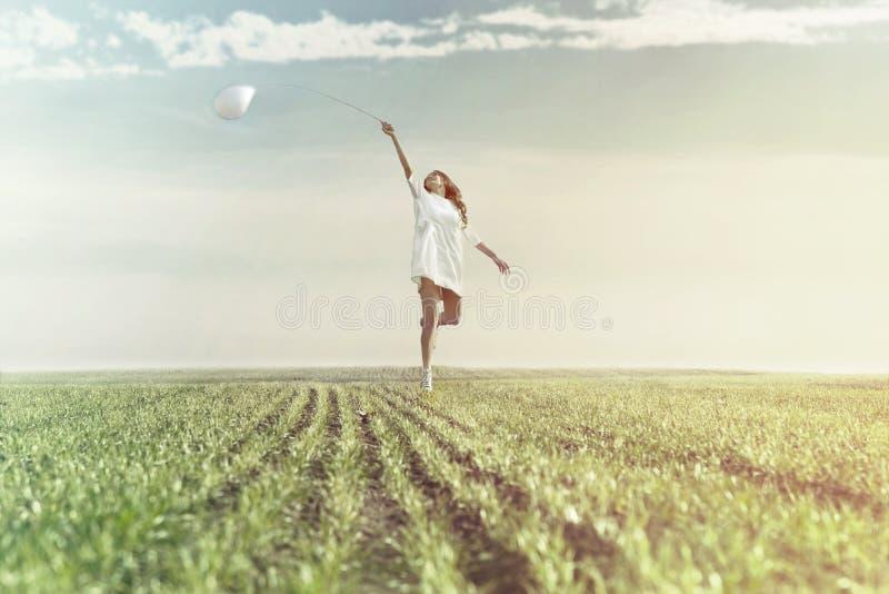 Den drömlika kvinnan kör lyckligt i mitt av naturen royaltyfri foto