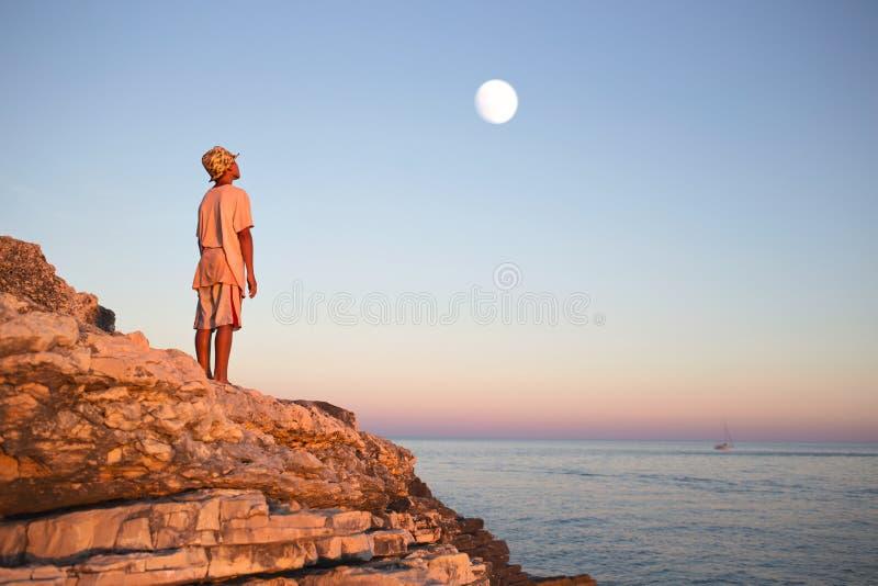 Den drömlika pojken beundrar den förtrollade månen i himlen arkivbild