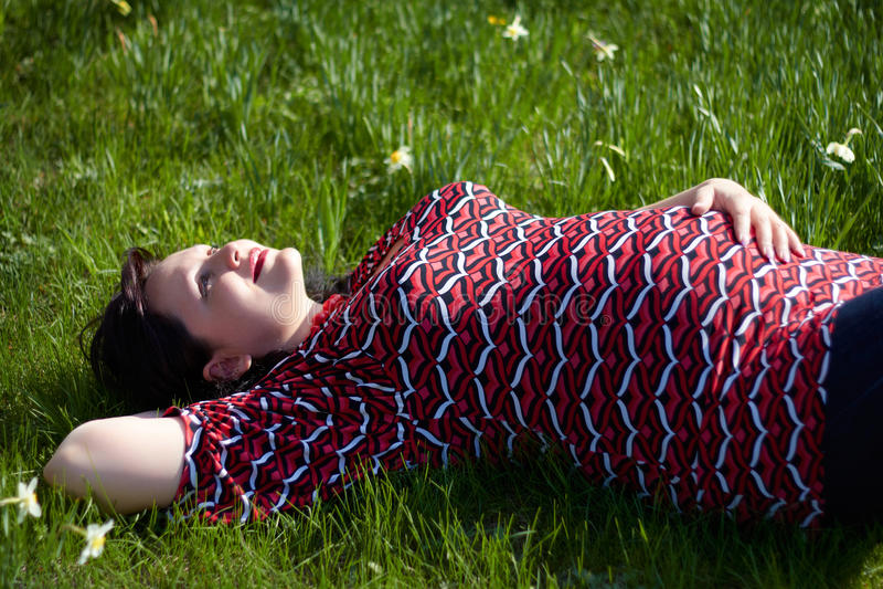Den drömma gravida flickan ligger på ett gräs arkivbilder