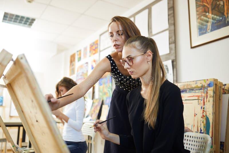 Den dra läraren hjälper den härliga unga flickan i den iklädda svarta blusen för exponeringsglas som sitter på staffli för att må arkivbild