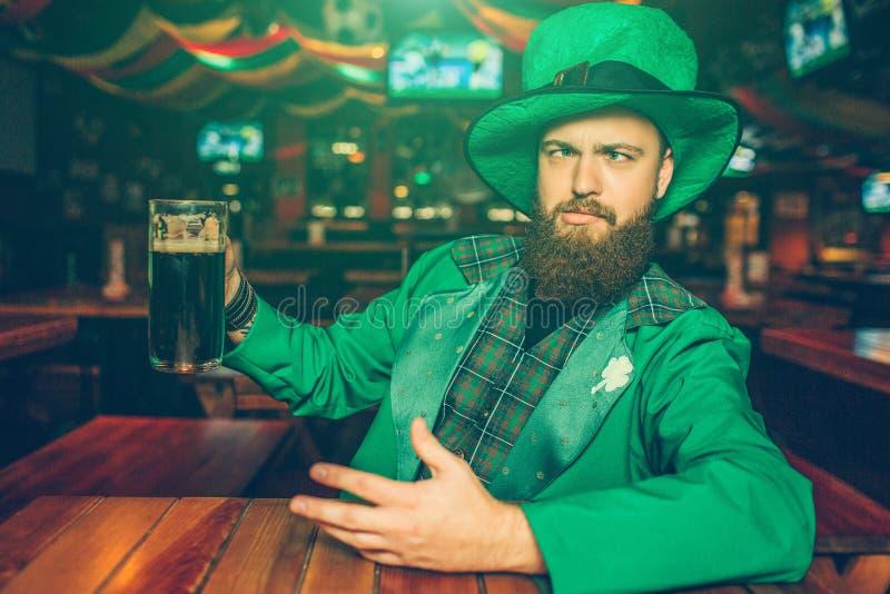 Den drack unga mannen i gröna Sts Patrick dräkt sitter på tabellen i bar Han rymmer rånar av mörkt öl Kyla för grabb royaltyfria bilder