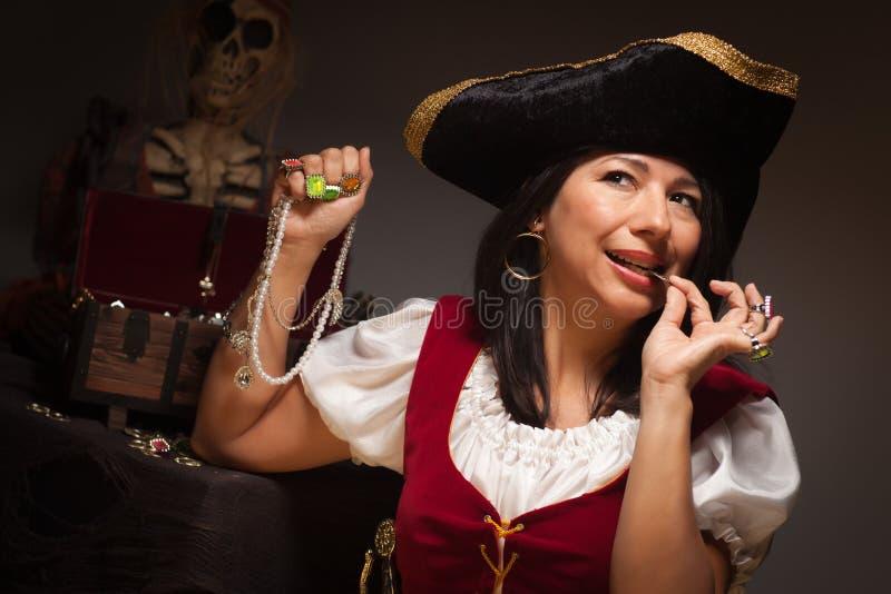 Den dramatiska kvinnlign piratkopierar att bita ett mynt royaltyfri fotografi